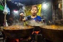 Mujer tailandesa cocinando comida callejera en Tailandia