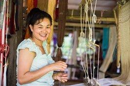 Mujer laosiana haciendo tejido según un método tradicional en Laos