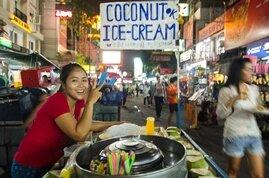 Una vendedora ambulante ofrece helado de coco en una calle de Bangkok